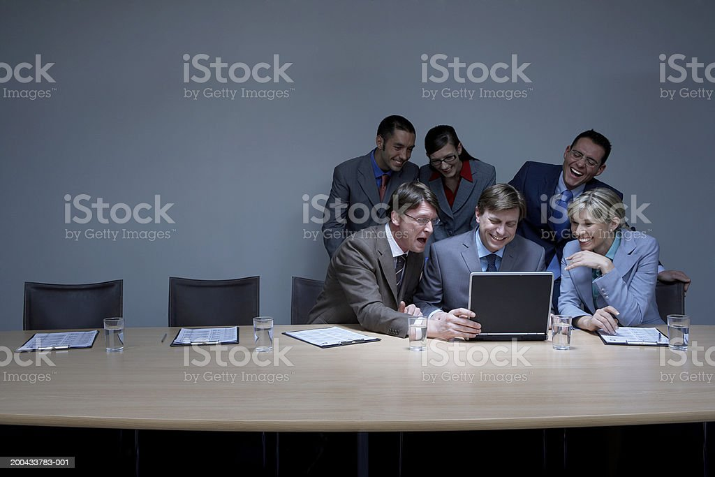 Six businessmen and businesswomen looking at laptop, laughing royalty-free stock photo