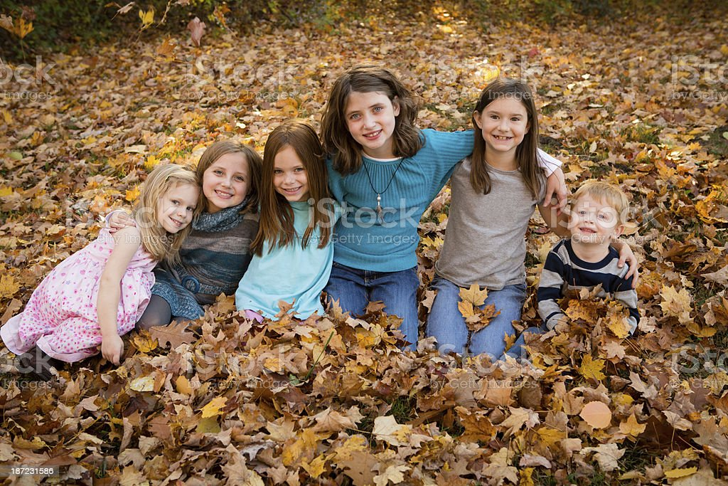 Six Children Sitting in Autumn Leaves Together royalty-free stock photo
