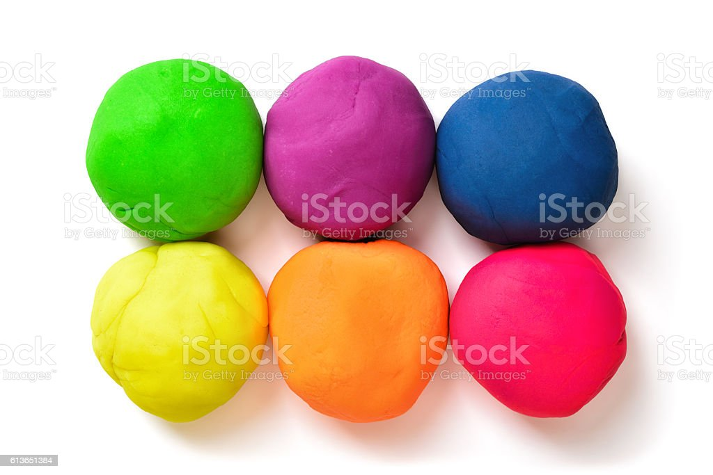Six colorful balls of modeling clay on a white background stock photo