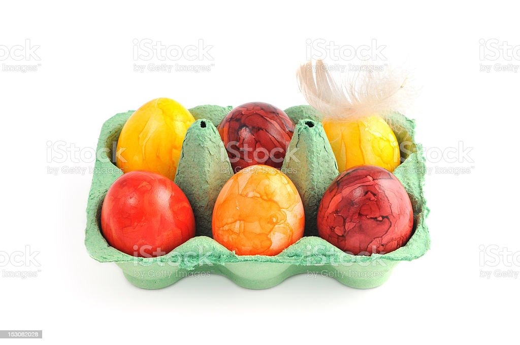 six colorful easter eggs with feather in green carton stock photo