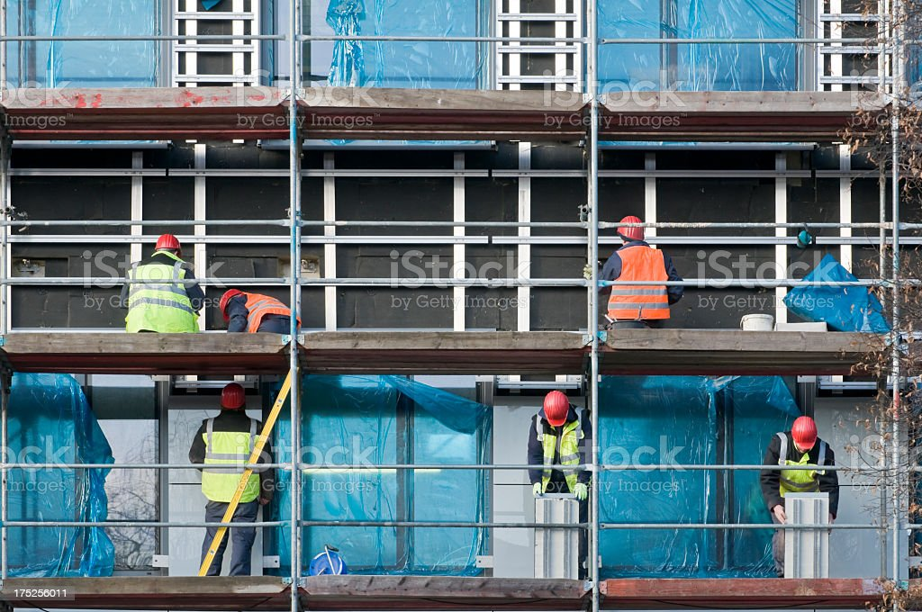 Six construction workers doing their job on scaffolding stock photo