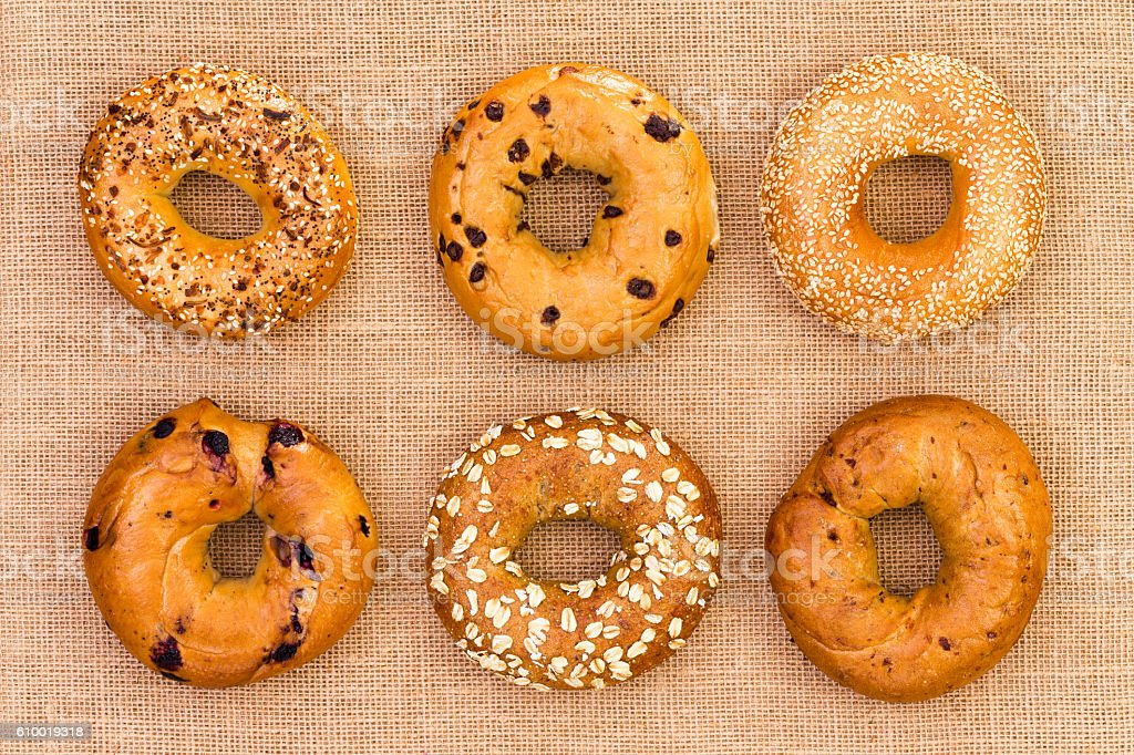 Six different tasty fresh bagels on burlap stock photo