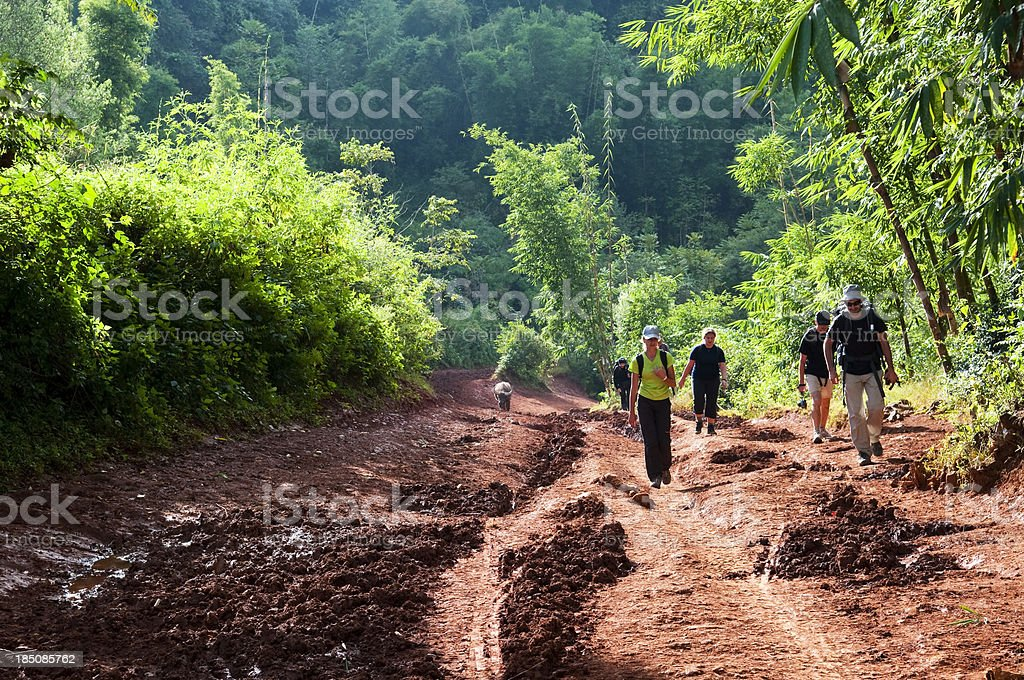 Backpackers hiking in Burmese countryside stock photo