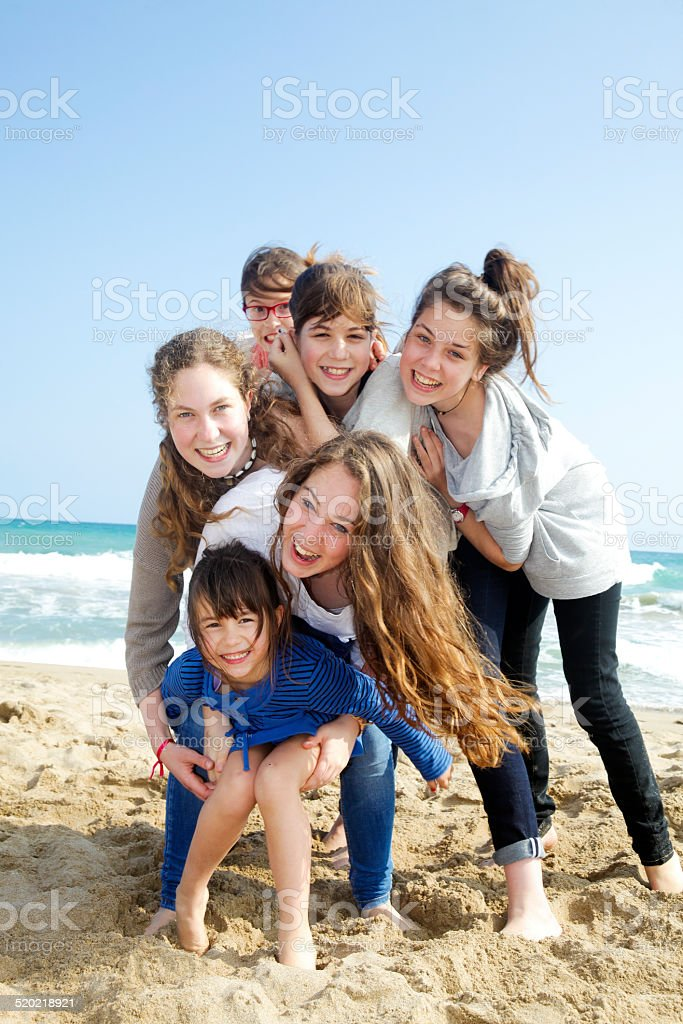 Six friends, all girls, playing in the beach stock photo
