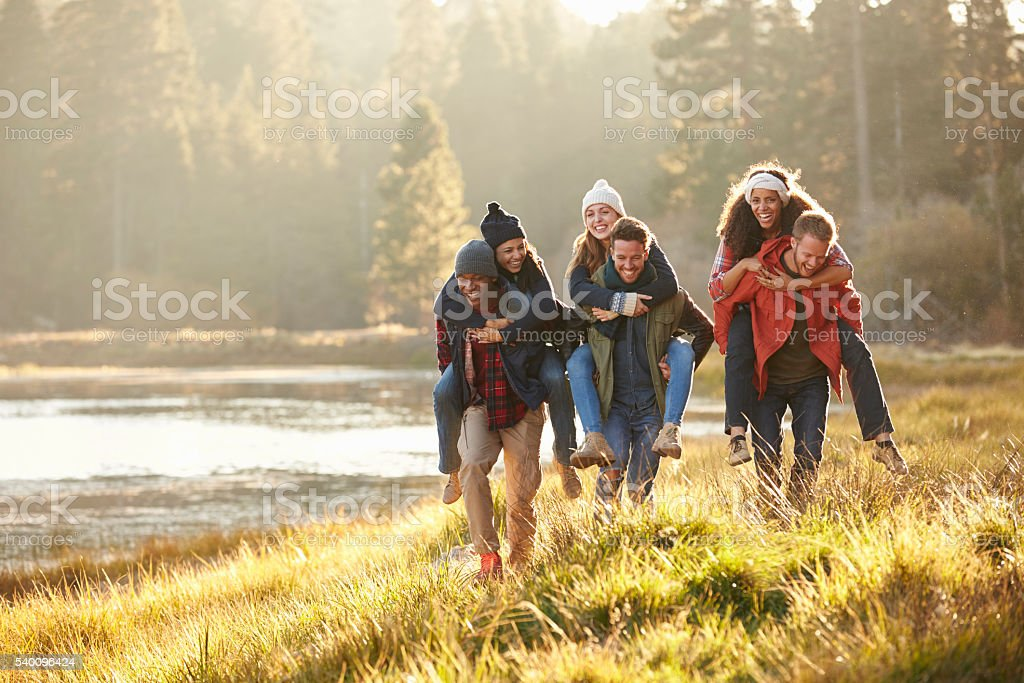 Six friends have fun piggybacking in the countryside by lake stock photo
