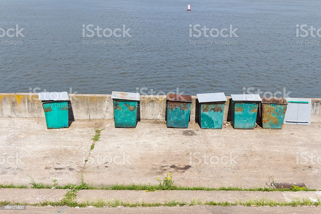 Six (6) green garbage containers standing on the stone embankmen stock photo