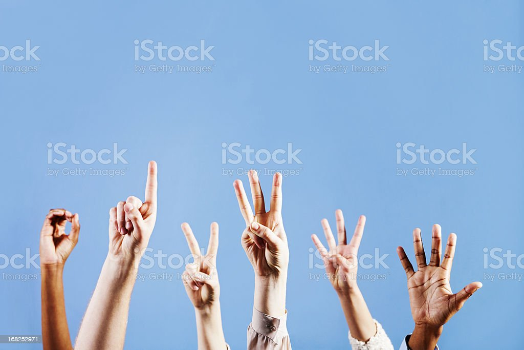 Six hands count from 0 to 5 against blue background stock photo