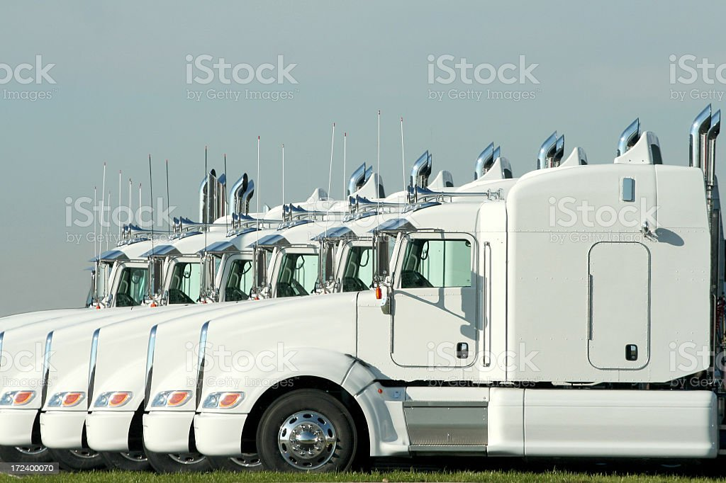 Six identical white semi trucks parked together stock photo