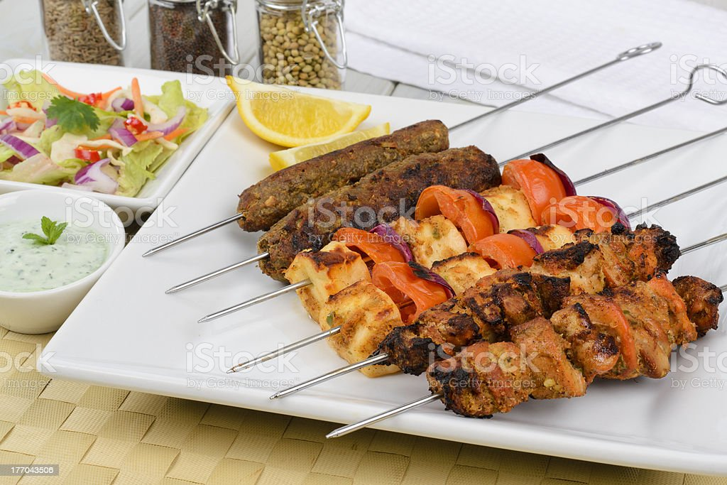 Six kebab skewers laid out on white square plate stock photo