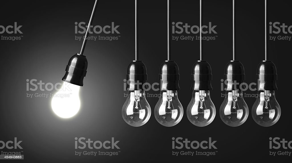 Six lightbulbs, one lit, in the form of Newton's cradle stock photo