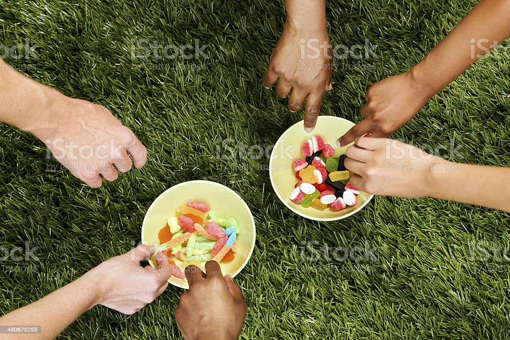 Six mixed hands grabbing candy; it's a sweet treat! royalty-free stock photo