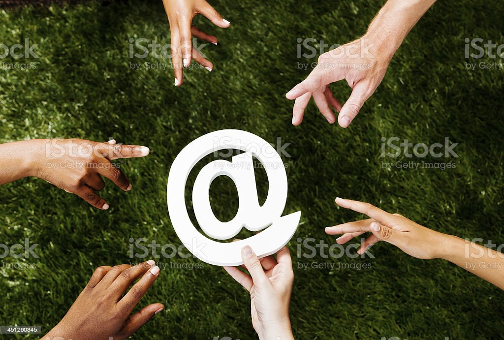 Six mixed hands reaching for @ sign royalty-free stock photo