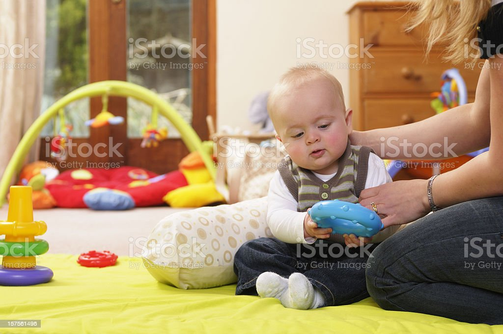 Six Month Old Baby Being Supported While Sitting And Playing stock photo