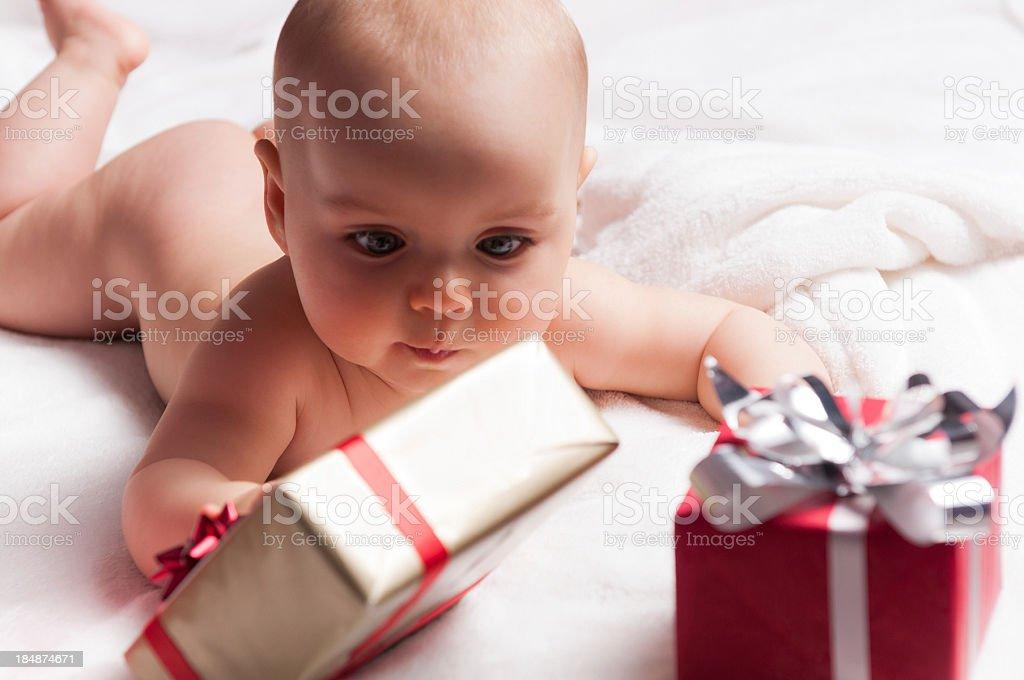 Six months old beautiful naked baby playing with gifts stock photo
