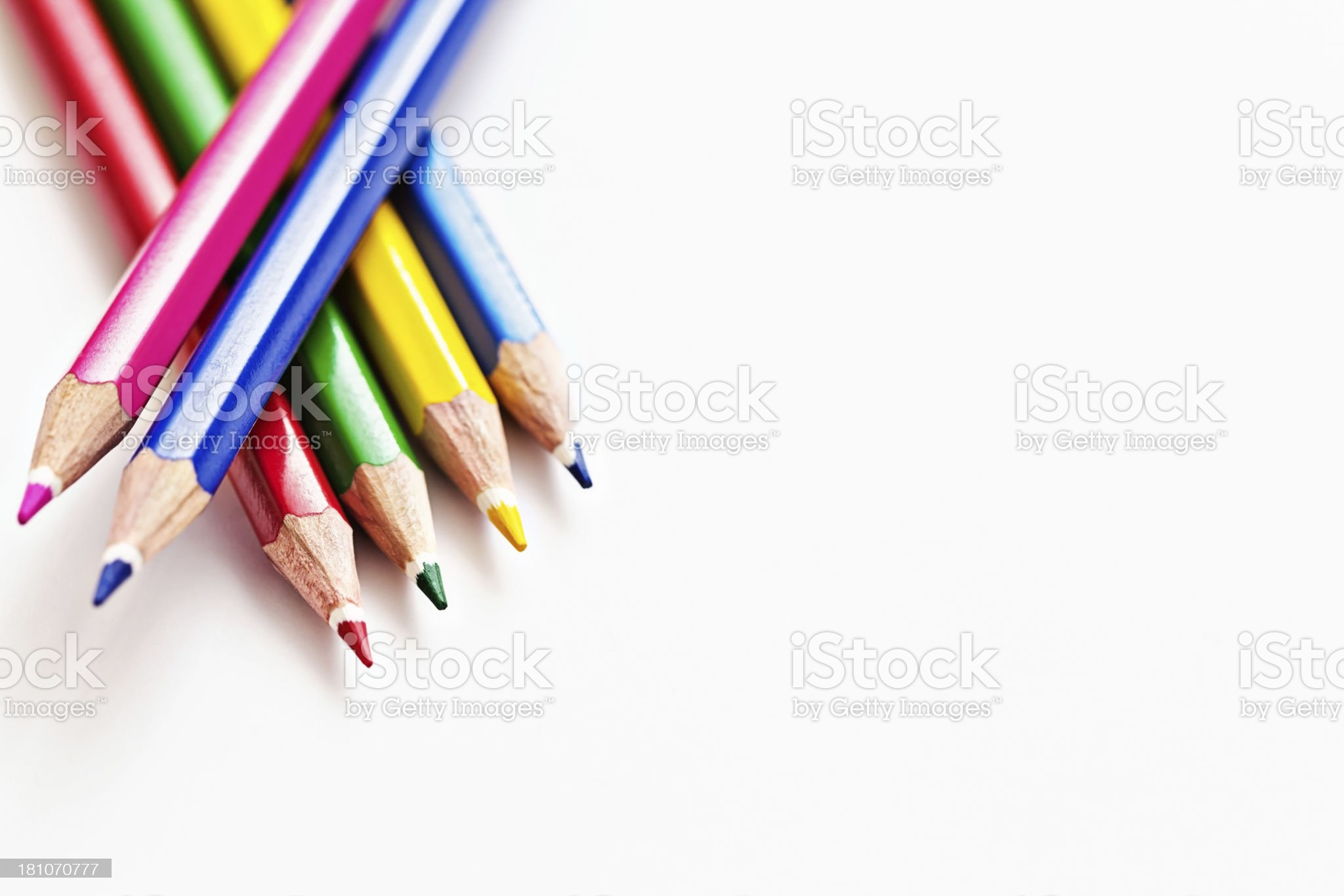 Six multi-colored pencil crayons stacked, pointing downwards, on white royalty-free stock photo