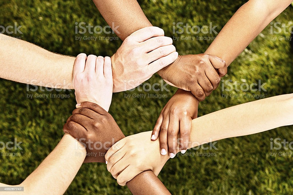 Six multiracial hands linked in harmony on grass stock photo