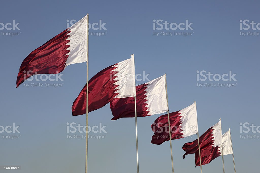 Six national flags of Qatar on a sunny day stock photo