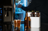 Six pack of brown beer bottles on kitchen counter