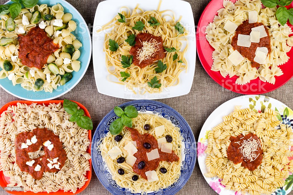 Six pasta dishes with sauce and herbs stock photo