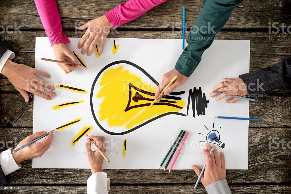 Six people drawing bright yellow light bulb on white paper stock photo