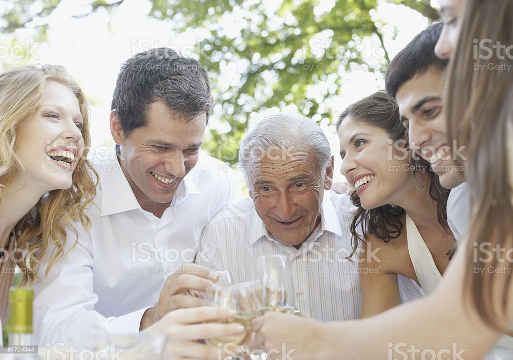 Six people outdoors toasting champagne and smiling royalty-free stock photo