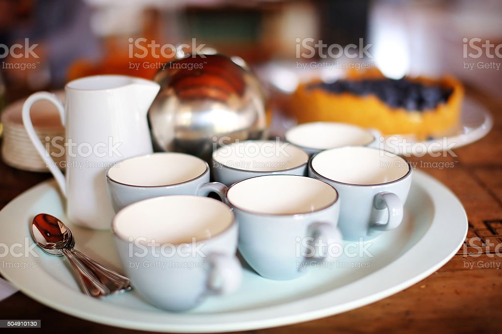 Six tea cups and a teapot stock photo