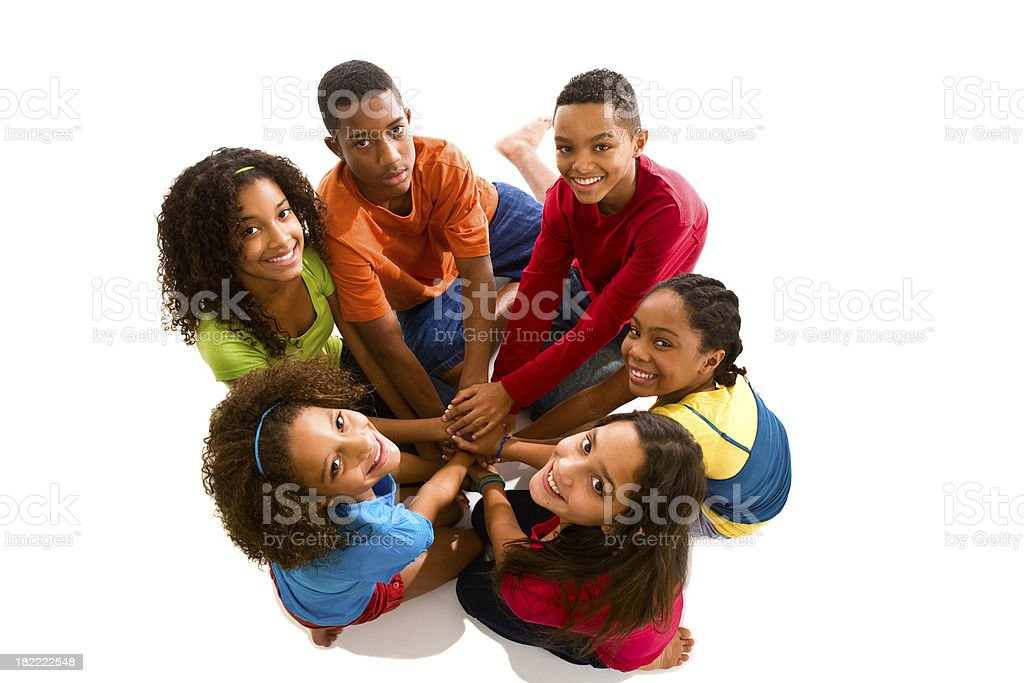 Six teenagers sitting in a circle hands stacked looking up royalty-free stock photo