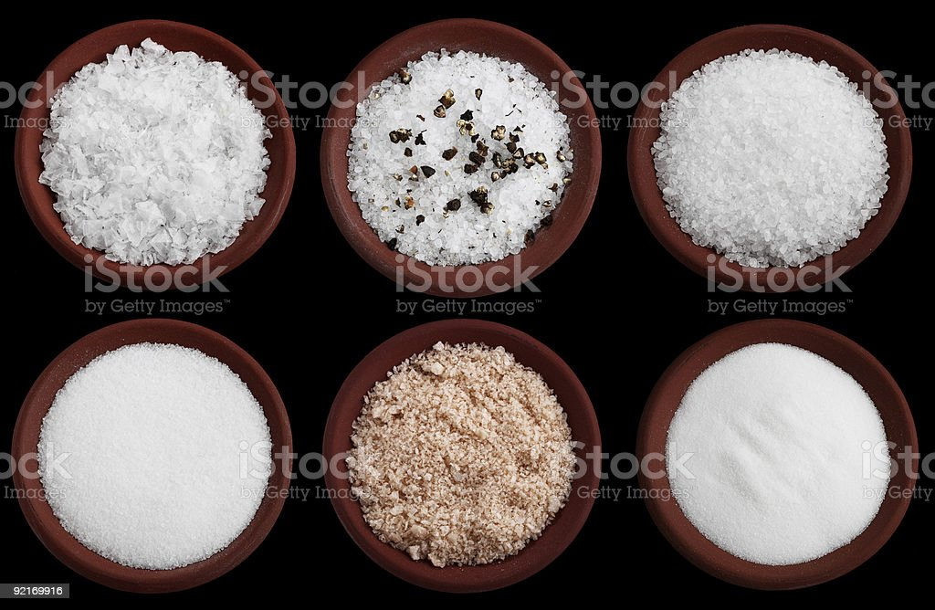 six terracotta plates with different  sea salt on black stock photo