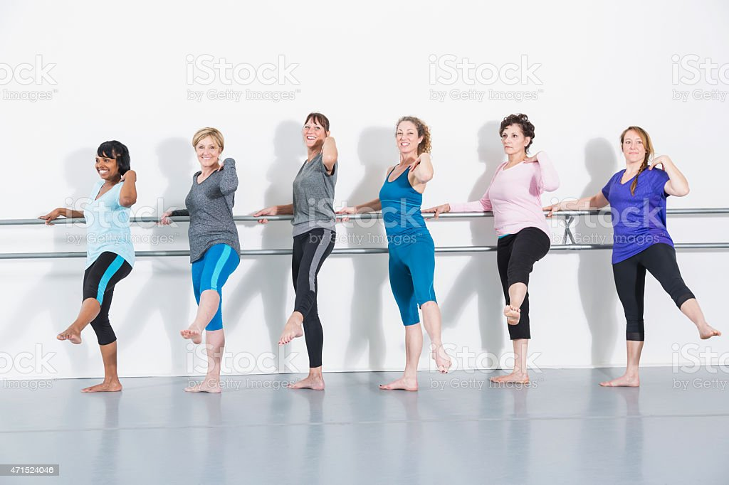 Six women doing barre exercises standing in a row stock photo