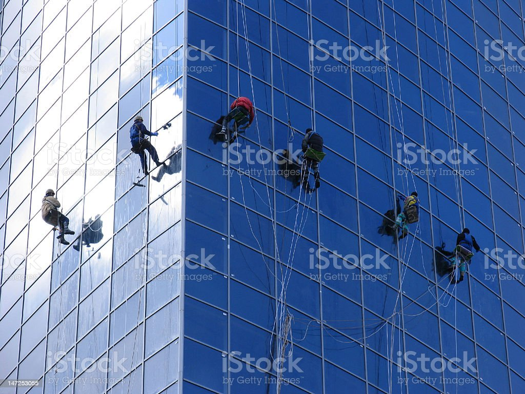 Six workers washing windows in the office building royalty-free stock photo