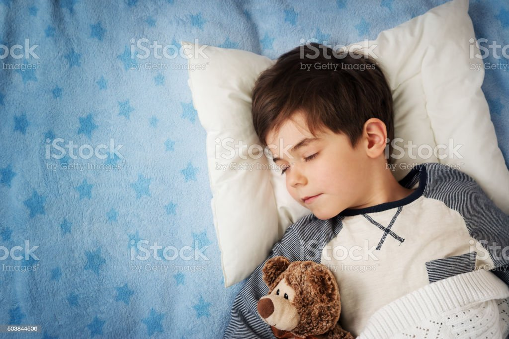 six years old child sleeping in bed with alarm clock stock photo