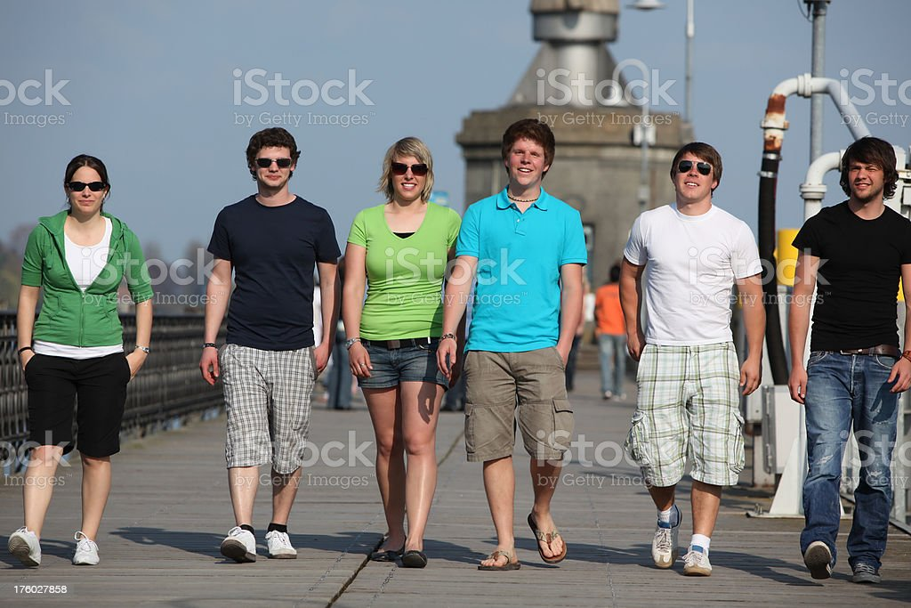 Six young people walking down the pier royalty-free stock photo