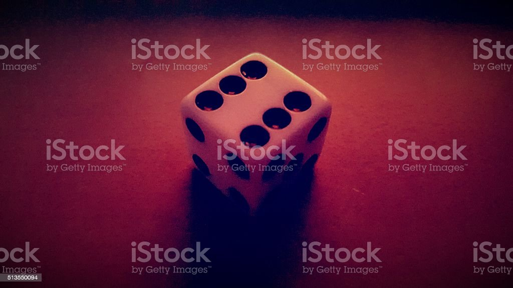 Six-Sided Die Under Red Light stock photo