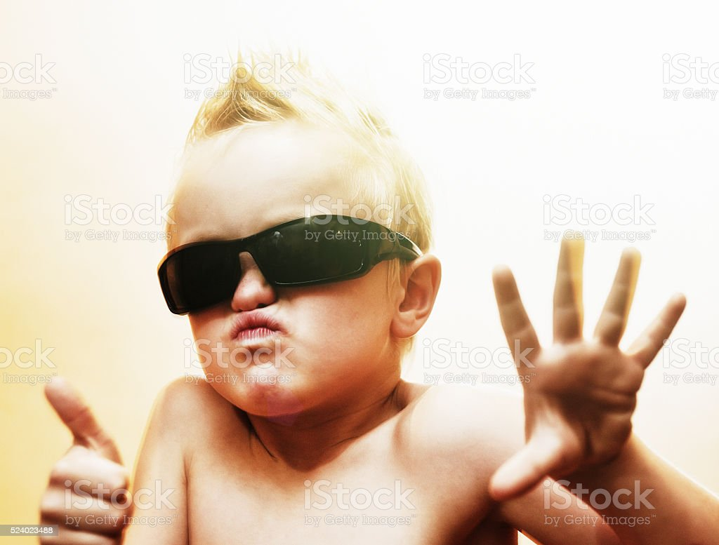 Six-year-old wannabe rock star in shades plays the part stock photo