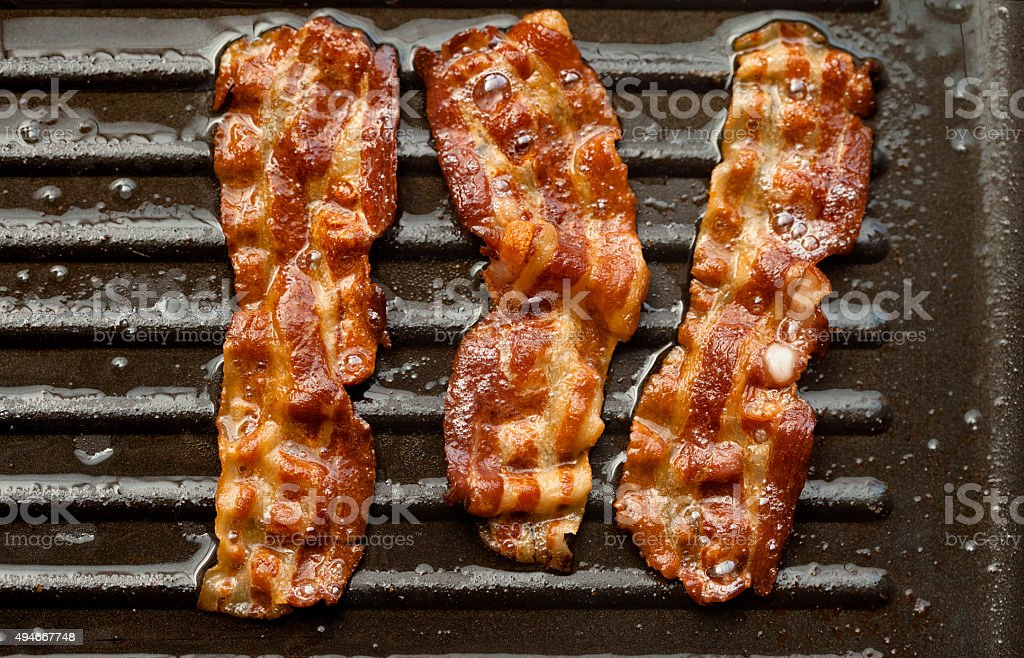 Sizzling Bacon Frying in a Pan stock photo