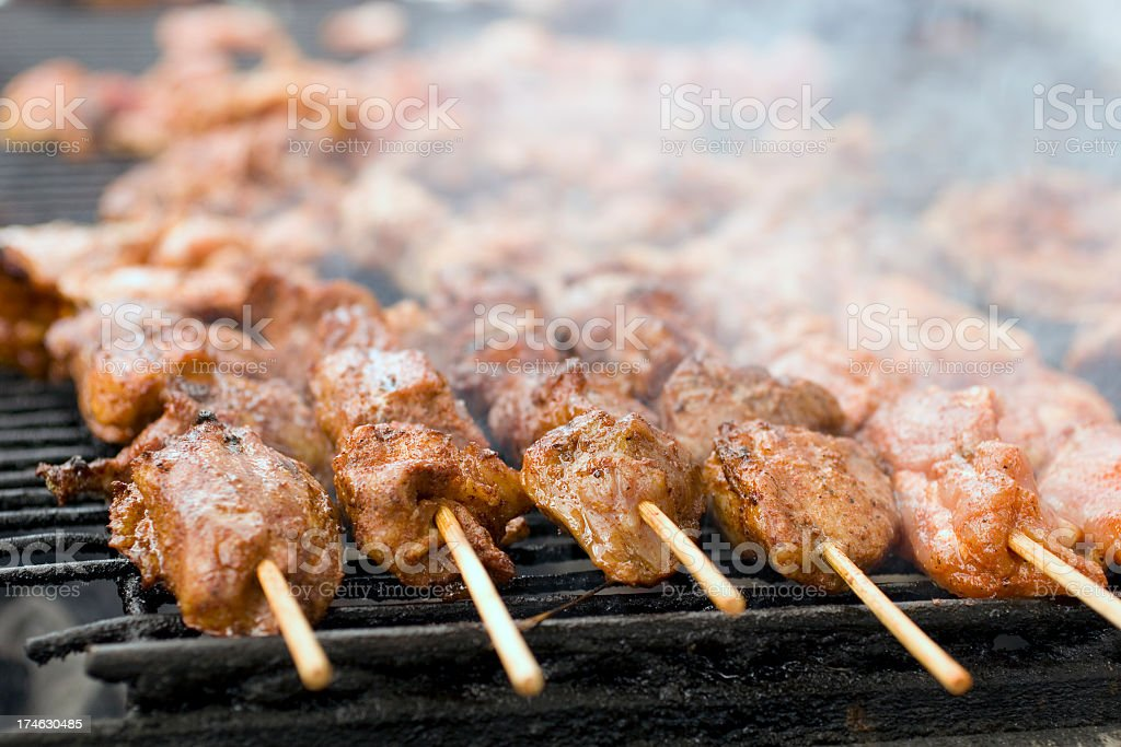 Sizzling meat on skewers cooking on a smoky barbeque grill stock photo