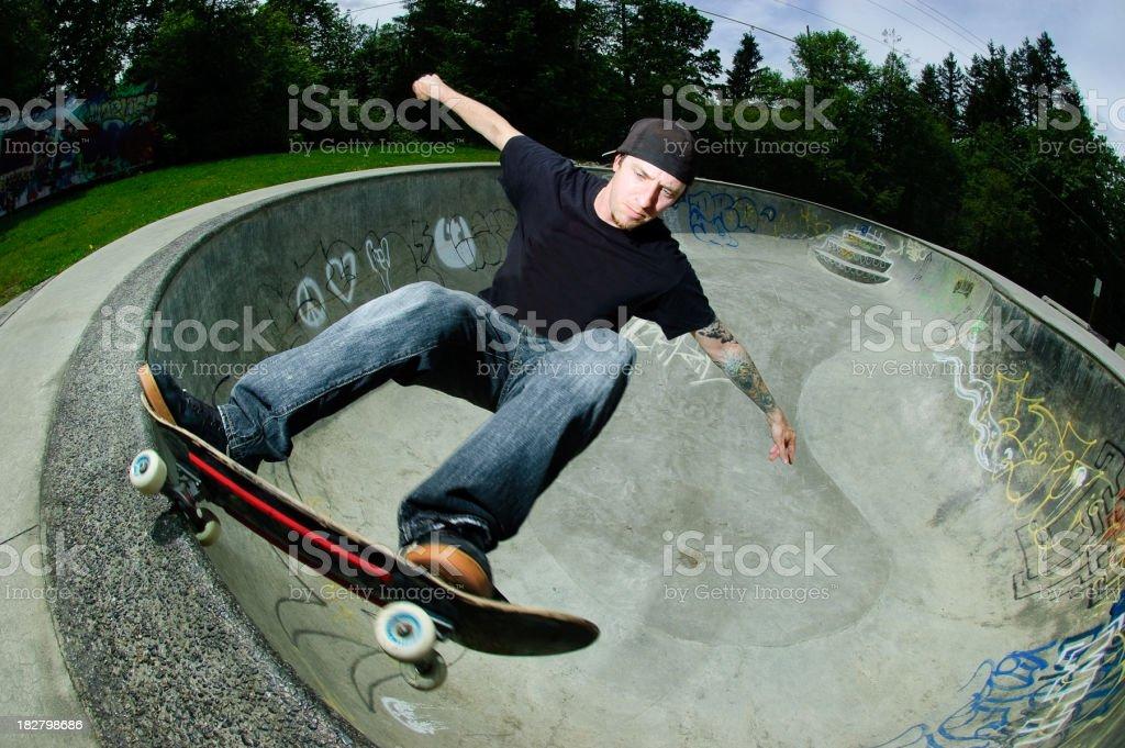Skateboard Frontside Grind in Pool stock photo