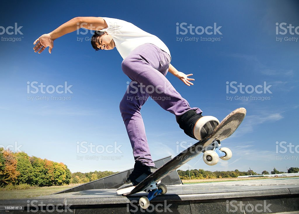 A skateboarder balancing on a curb under blue sky royalty-free stock photo