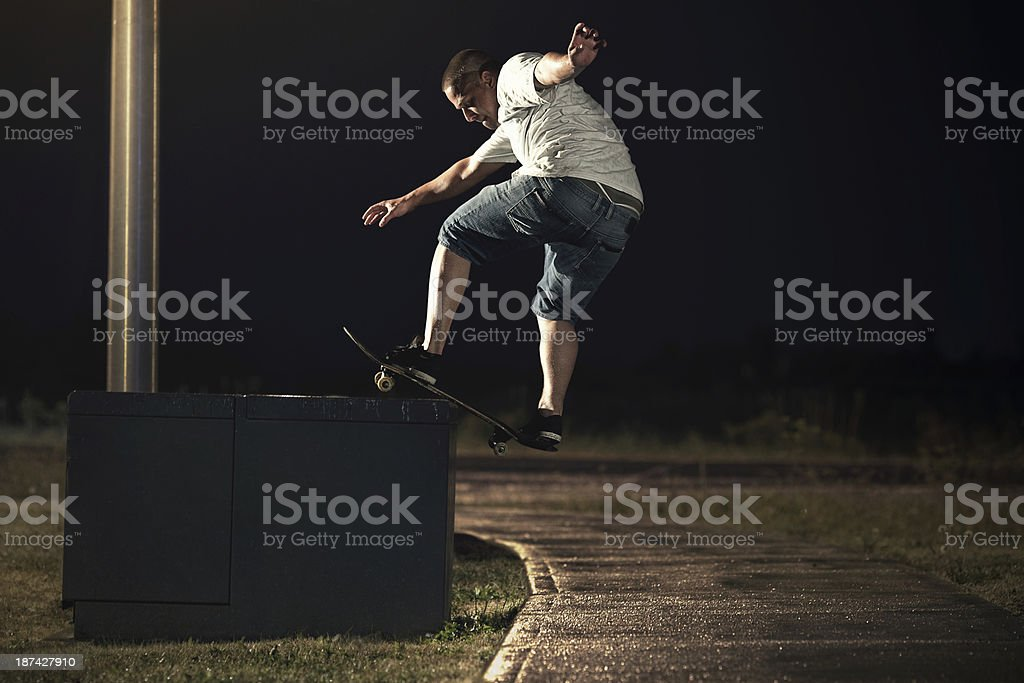 Skateboarder doing a Frontside Boardslide trick at night stock photo