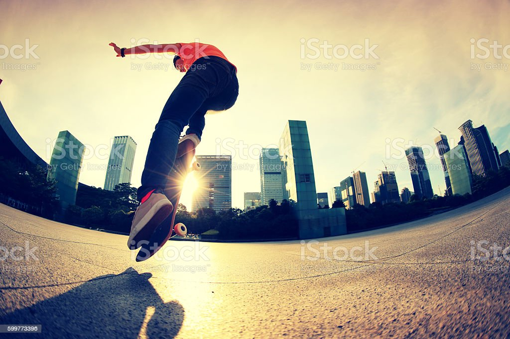 skateboarder doing an ollie trick at sunrise city stock photo