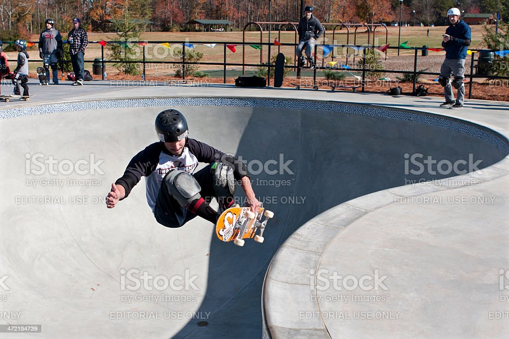 Skateboarder Grabs Board Doing Trick In Big Bowl stock photo