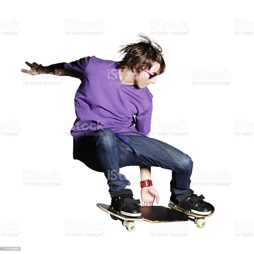 Skateboarder in purple shirt and jeans caught mid-air royalty-free stock photo