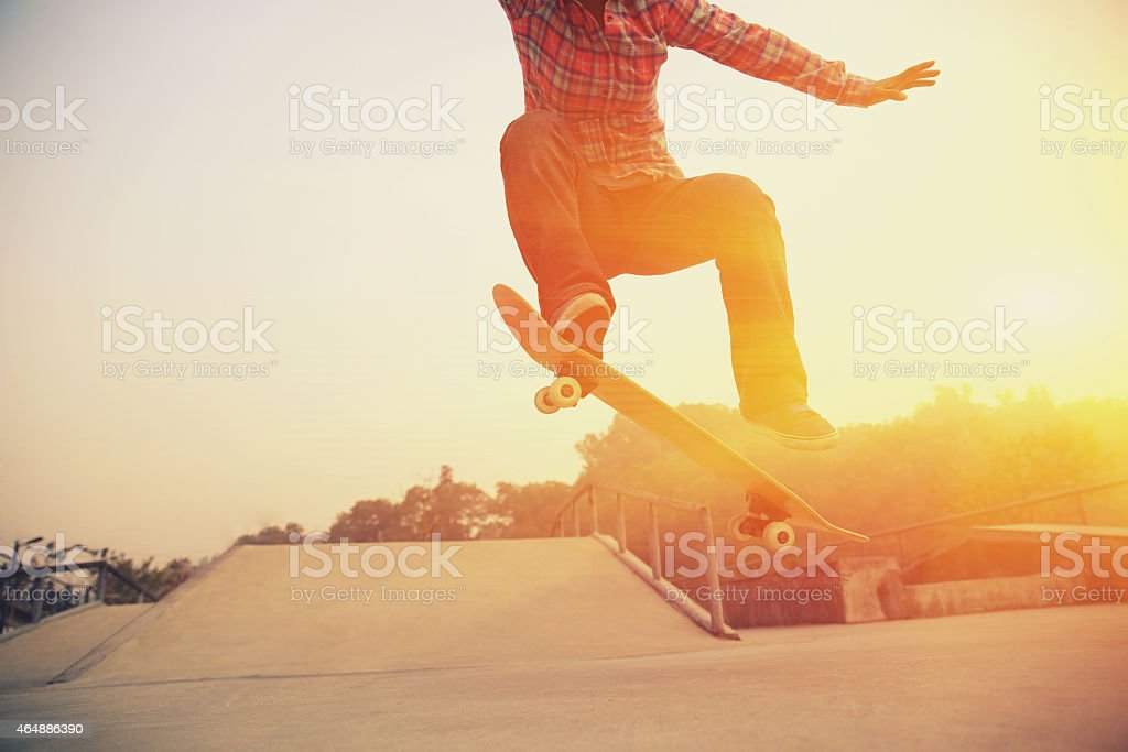 A skateboarder jumping his board at a skate park at sunset  stock photo