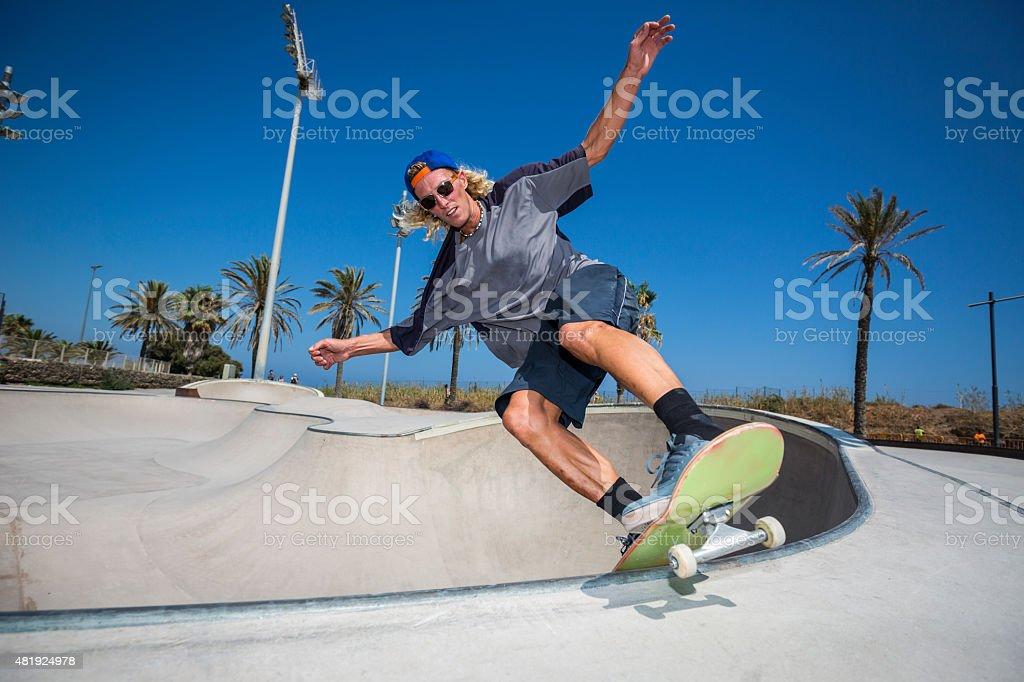 Skateboarder jumping in skatepark stock photo
