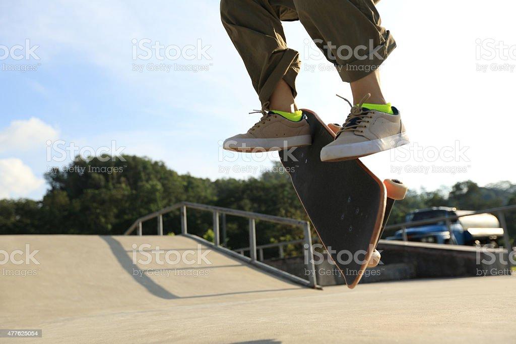 skateboarder legs doing a trick heel flip at skatepark stock photo