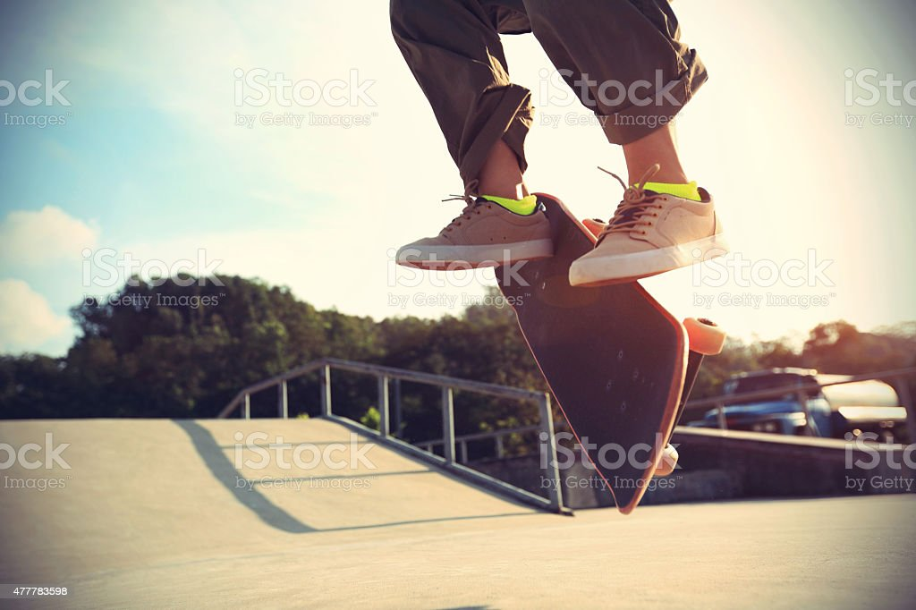 skateboarder legs doing a trick heelflip at skatepark stock photo