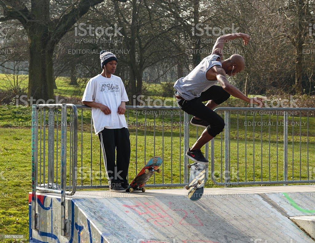 Skateboarder on ramp doing flip kick stock photo