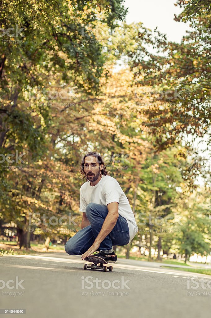 Skateboarder squatting on a skateboard and ride through the forest stock photo