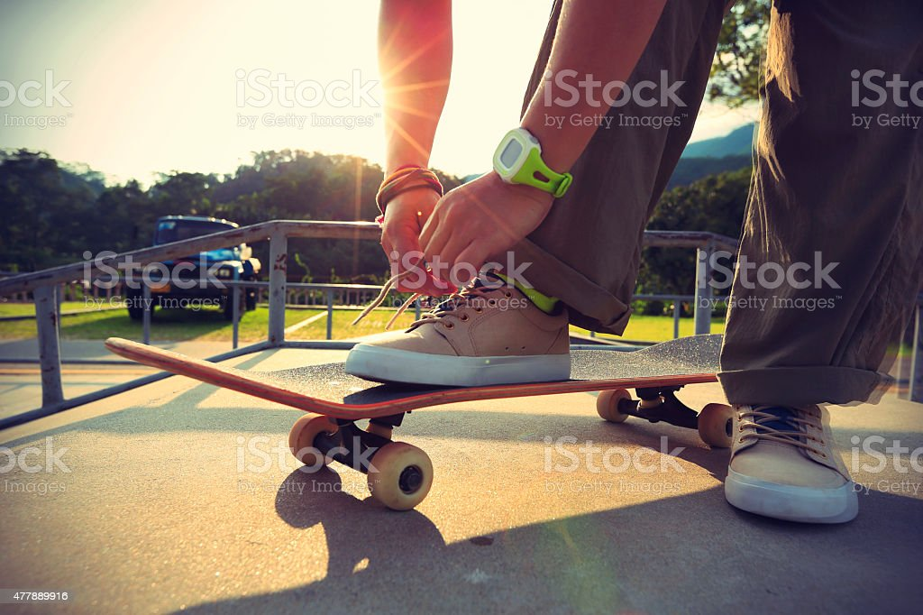 skateboarder tying shoelace at skatepark stock photo