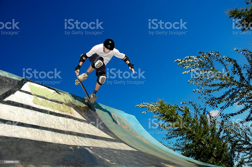 A skateboarder wearing gear in action on an outdoor ramp stock photo